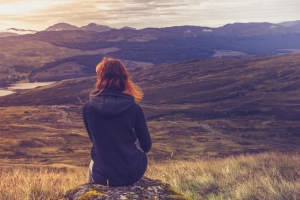 Woman sitting on mountain top and contemplating the sunset