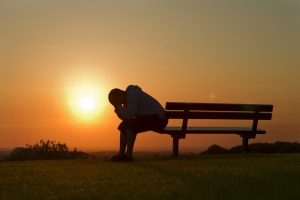 Portrait of an unhappy person sitting on a bench at sunset