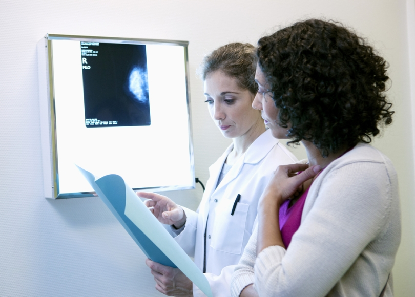 Woman of color discussing breast cancer disparities with a doctor